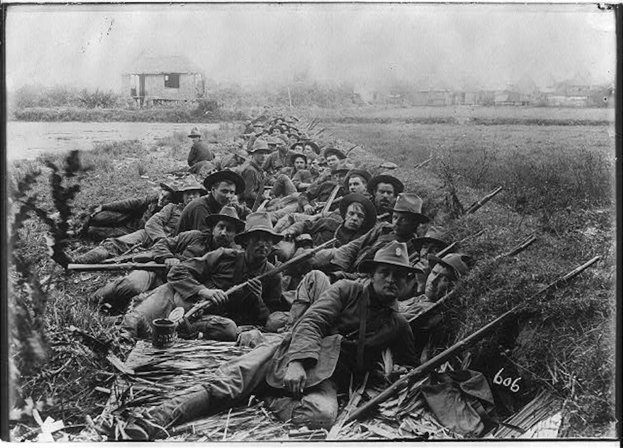 Dozens of soldiers with guns lay in a trench.