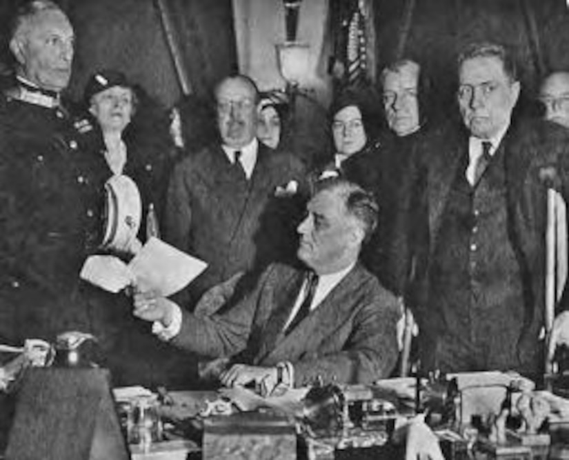 A seated man hands a standing man a piece of paper while others watch from behind.