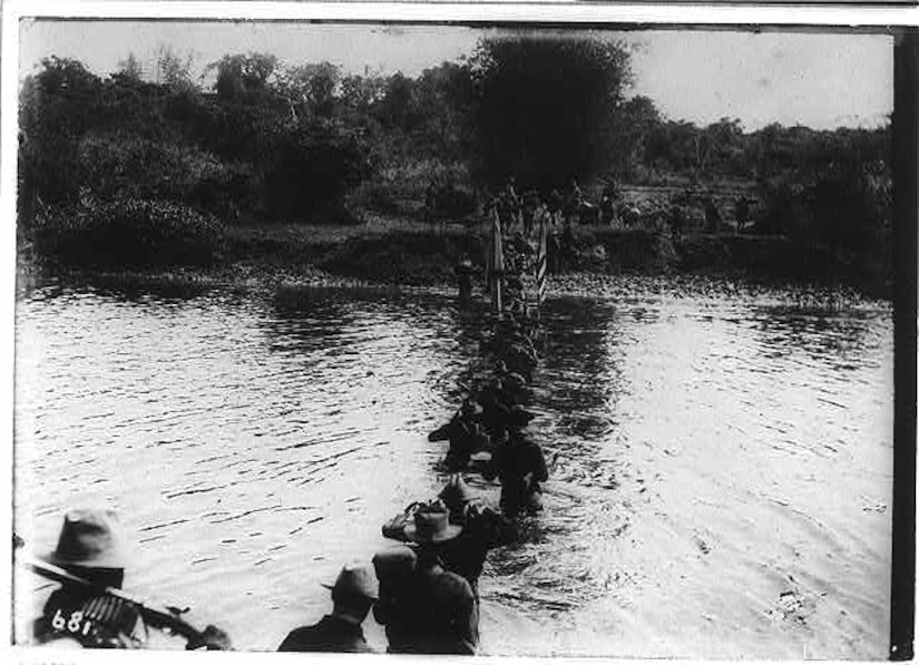 A row of men cross a waist-high river.