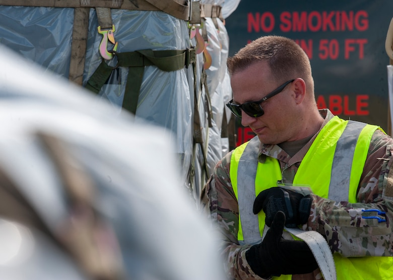 U.S. Air Force Master Sgt. Michael A. Smith, the 6th Logistics Readiness Squadron cargo deployment function NCO in charge, holds onto a pallet strap on the flightline, Oct. 21, 2020 at MacDill Air Force Base, Fla. The orientation of the pallet when it is loaded determines where the straps go, to prevent items from sliding around during transportation. (U.S. Air Force Photo by A1C David D. McLoney)