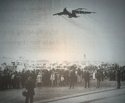 A very old image with a crowd in front and in the top of the image you can see a C-5 with its landing gears open about to land on the flight line.