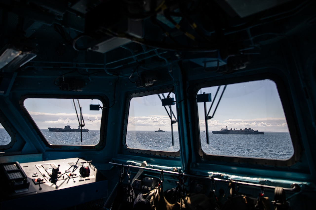 Three ships can be seen from the windows on the bridge of a fourth ship.