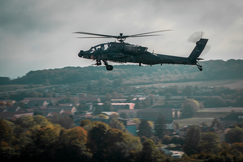 An Apache helicopter flies over town.