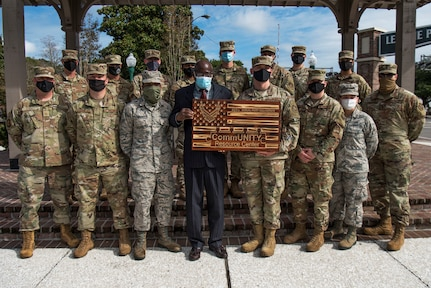 The Community Resource Center Summerville presents members of the 437th Aerial Port Squadron with a plaque during a recognition ceremony, Oct. 23, 2020, in Summerville, S.C. Members of both Joint Base Charleston and the community came together to honor the volunteer efforts of these Airmen who have been instrumental in the massive food giveaways orchestrated by the Summerville YMCA and the Community Resource Center Summerville where they helped provide over 60,000 boxes of groceries and 2,400 kits of school supplies to Dorchester County Residents since the beginning of the pandemic.  (Photo by Staff Sgt. Tenley Long)