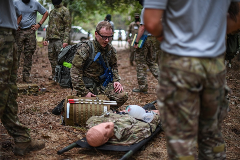 Special Operations Surgical Team candidates participate in a medical scenario providing emergency medical assistance to a subject on the leaf-covered ground in a woods