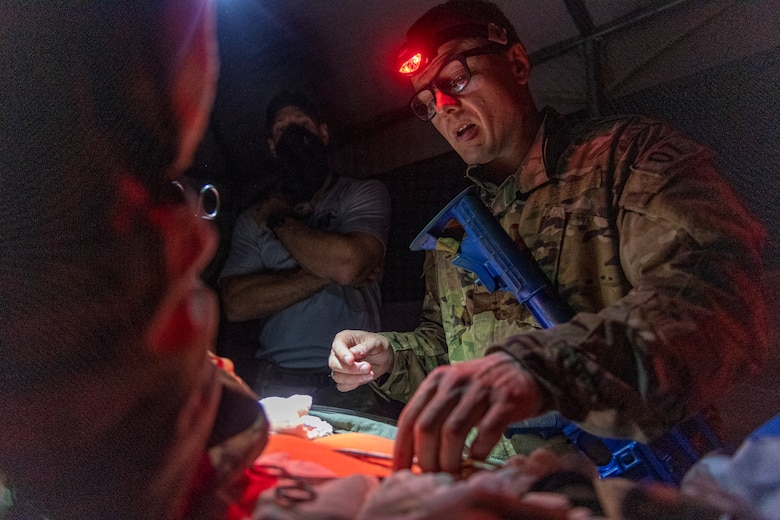 Special Operations Surgical Team candidates participate in a medical scenario operating on a subject in low light