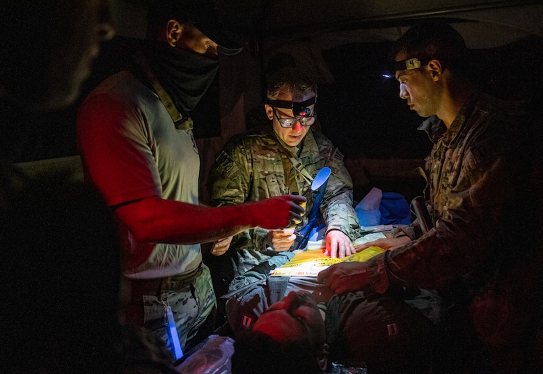 Special Operations Surgical Team candidates participate in a medical scenario operating in low light.