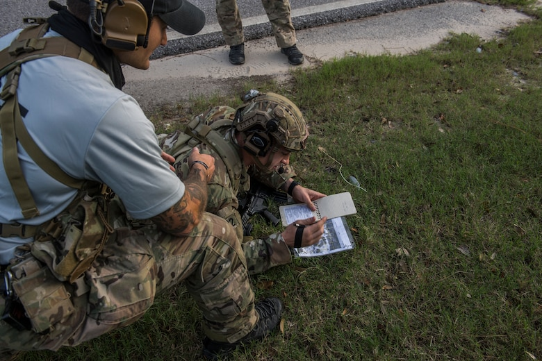A pair of tactical air control party candidates participate in a call for fire scenario. One crouches on the ground looking at a map while a light-blue shirted cadre member kneels beside him and talks on his headset.