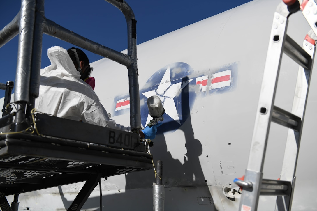 U.S. Air Force Airman 1st Class Tracy Bethea, 509th Maintenance Squadron low-observable maintenance technician, paints around the Air Force Roundel at Whiteman Air Force Base, Missouri, Oct. 13, 2020. The body of the Boeing B-47 Stratojet static aircraft had to be sanded down during restoration before any painting could begin. (U.S. Air Force photograph by Airman 1st Class Devan Halstead)