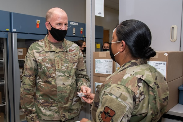 Vice Chief of Staff of the Air Force Gen. Stephen W. Wilson presents a decorative coin to Master Sgt. Simone Moonsammy-Robinson to show appreciation for her contribution to the COVID-19 response during a visit to the 42nd Medical Group, Oct. 22, 2020, Maxwell Air Force Base, Alabama. Moonsammy-Robinson developed a plan to make the packaging and shipment of COVID-19 tests more efficient and standardized. (U.S. Air Force photo by William Birchfield)