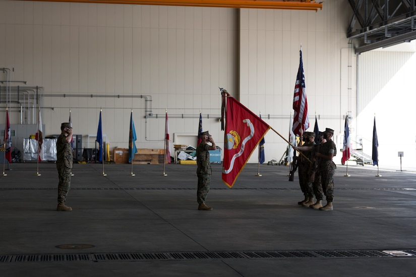 Marines stand in formation; some hold flags.
