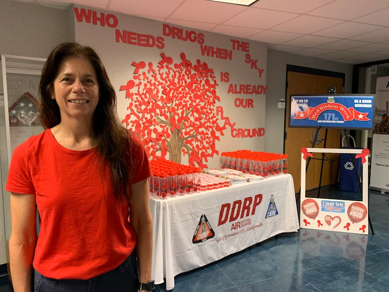 Kim Rose poses in front of a red ribbon week display