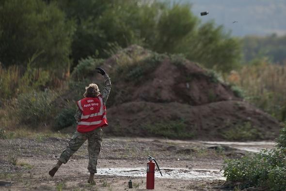An Airman throws a smoke grenade.