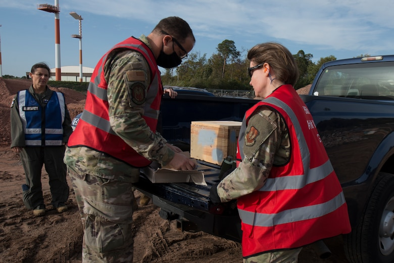 An Airman gives smoke grenades and ground burst materials to another Airman.