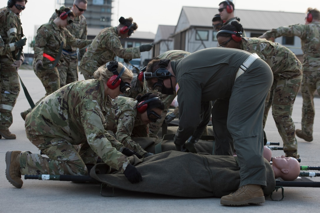 Airmen secure simulated victims to stretchers.
