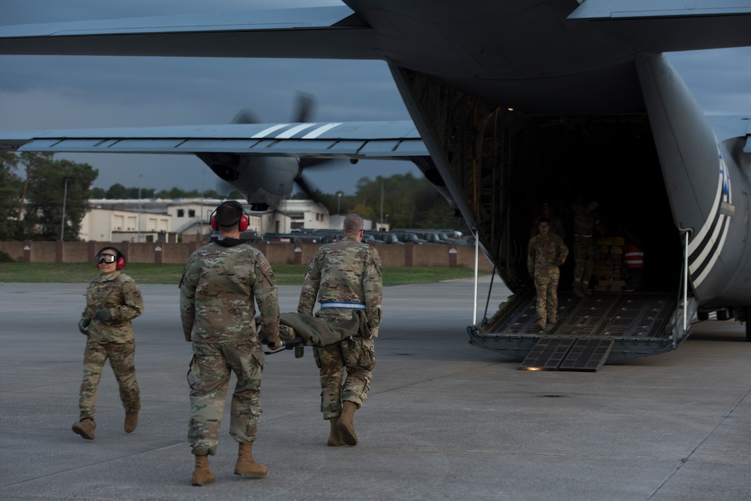 Airmen transport simulated victims to a C-130J Super Hercules.