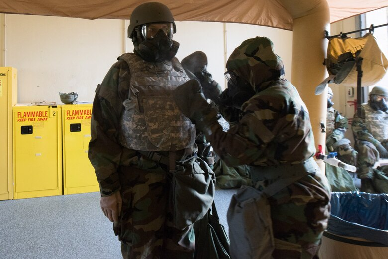 An Airmen simulates the decontamination of another Airmen.