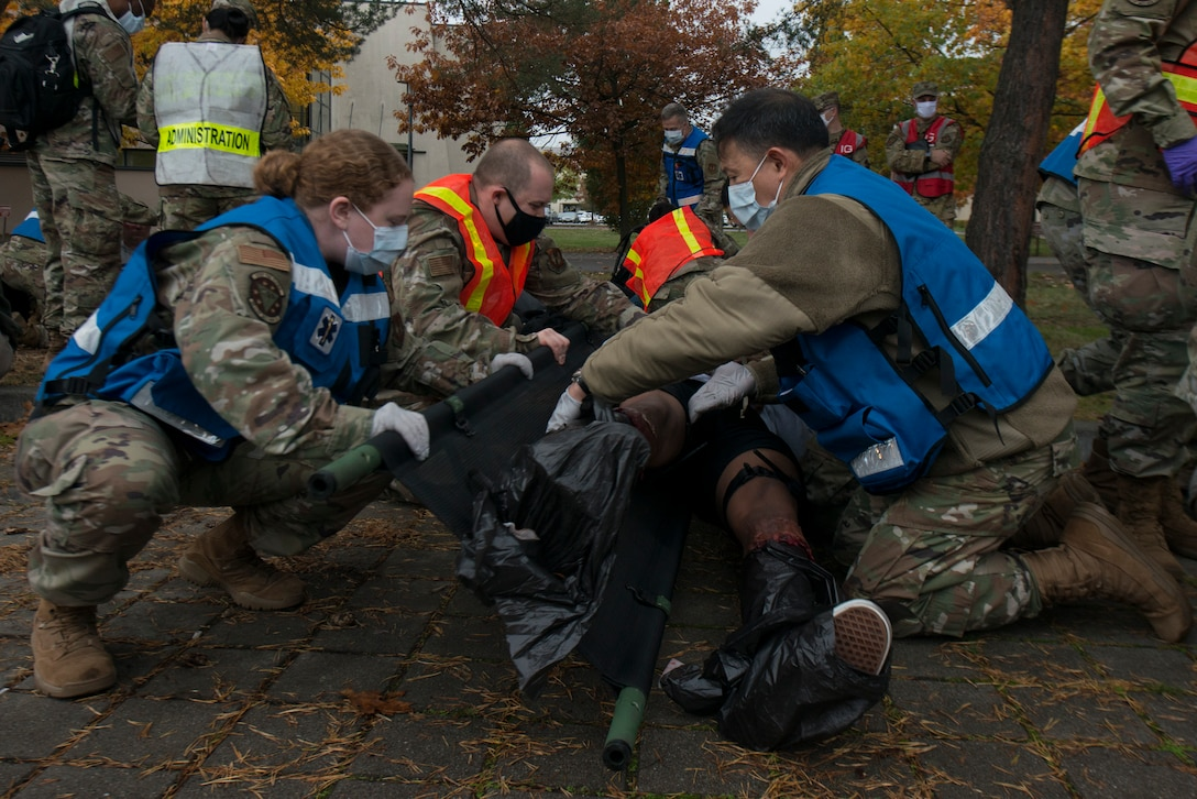 Medical Airmen transfer a simulated victim to a stretcher.