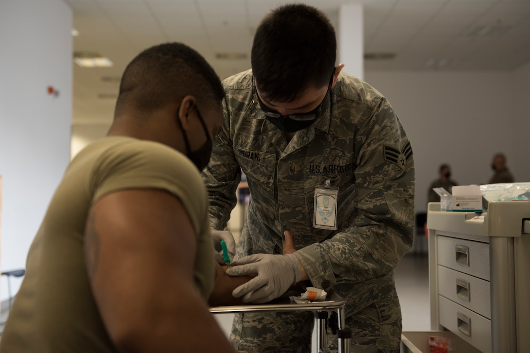 An Airman draws blood from another Airman.