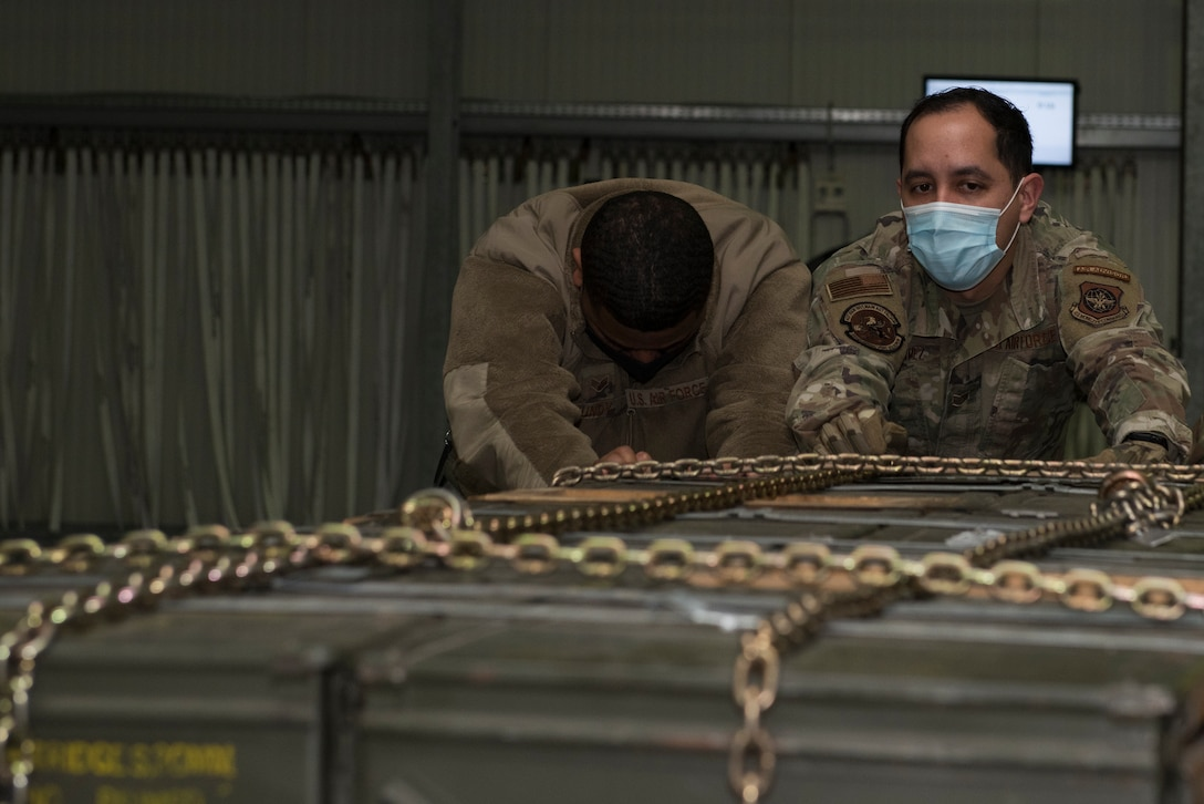 Airmen push an ammunition pallet.