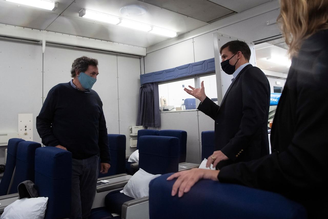 Defense Secretary Dr. Mark T. Esper speaks to people on a plane.
