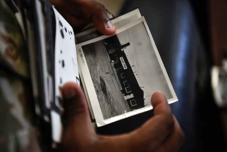 A photo of an Airman holding an old photo from the 1960s.