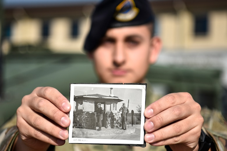 A photo of an Airmen holding a photo from the 1960s.