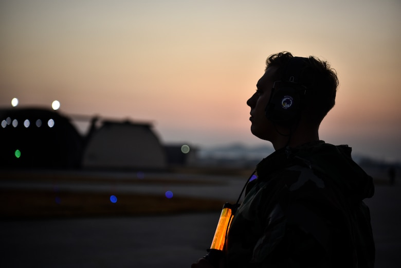 A photo of a crew chief standing on the flightline.