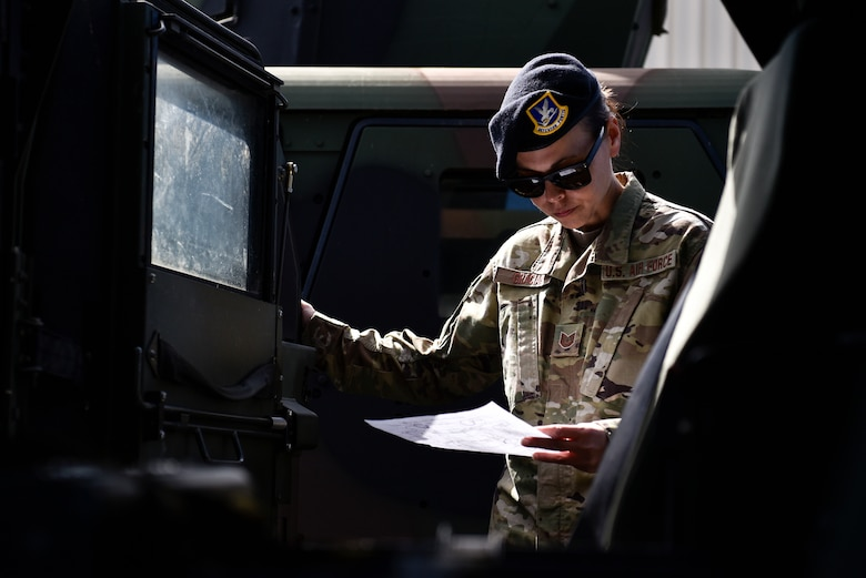 A photo of an Airman inspecting a Humvee.
