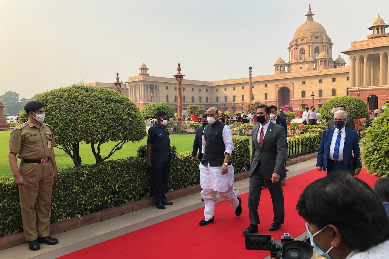 Two men walk on a red carpet while others stand at attention.
