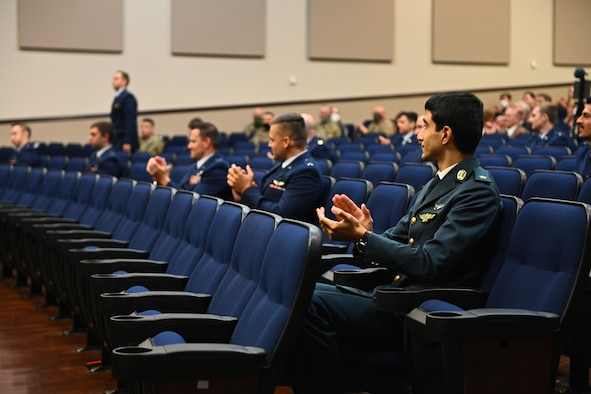 U.S. Air Force and international student pilots from class 21-01 clap for one of their fellow classmates heading to the stage Oct. 23, 2020, on Columbus Air Force Base Miss. As a result of COVID-19 restrictions the graduation was live streamed to Facebook on the Columbus AFB page for viewers not in attendance. (U.S. Air Force photo by Senior Airman Jake Jacobsen)