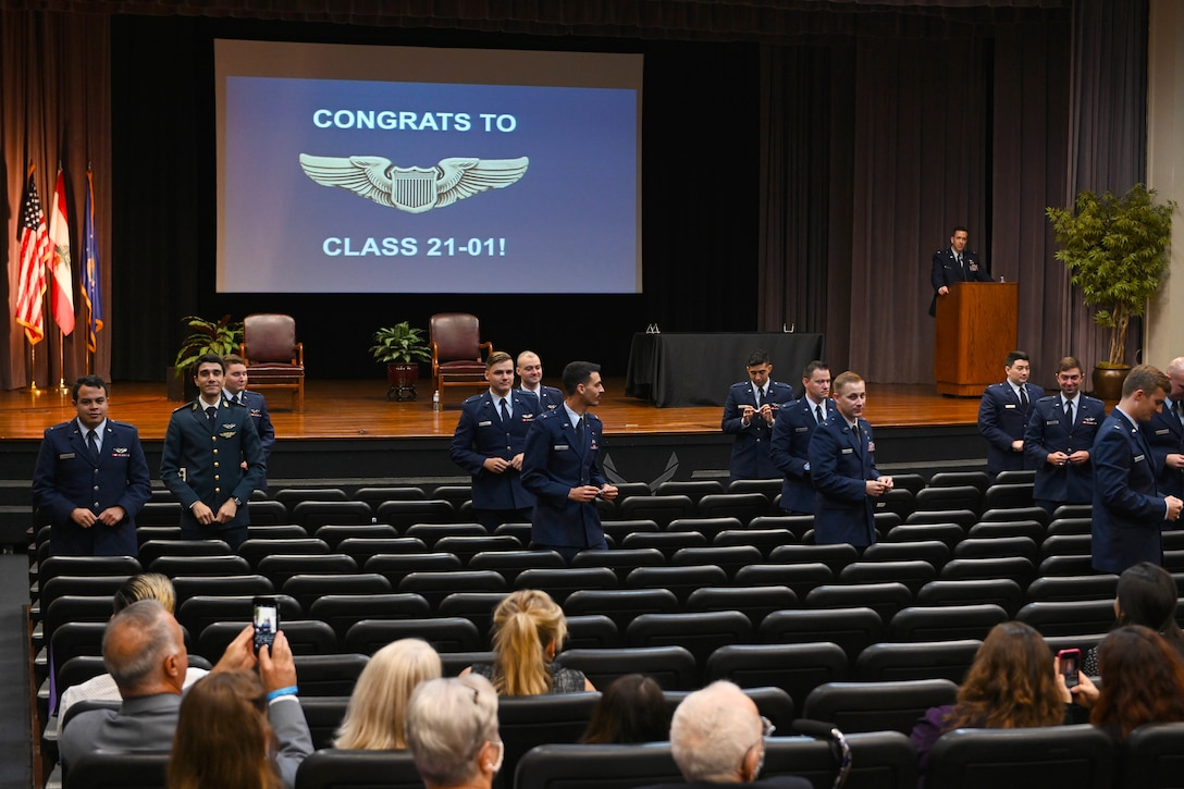 The graduating class of 21-01 stands to break their silver wings in half Oct. 23, 2020, on Columbus Air Force Base Miss. The traditional breaking of the wings symbolizes the sacrifice made to the pilots who put their lives on the line for their country. The two halves are never to be brought together again while the pilot is alive. (U.S. Air Force photo by Senior Airman Jake Jacobsen)