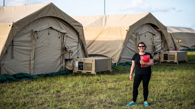 U.S. Air Force Chrissie Reilly, 366th Fighter Wing historian, holds her notebook while standing in the mobile operating base during Agile Flag 21-1 at Tyndall Air Force Base, Florida. Reilly conducts interviews, records observations and collects images that can be used for after-action reports and archived for historical record. (U.S. Air Force photo by Senior Airman Andrew Kobialka)