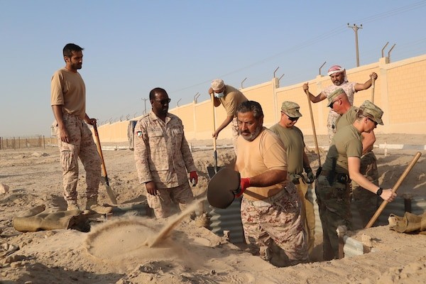 Soldiers from Forward Support Company, 891st Engineer Battalion, team up with soldiers from the Kuwaiti Land Forces to reconstruct fighting positions in the Land Force Institute's combat course Oct. 7, 2020. Soldiers from both nations will continue to partner throughout October.