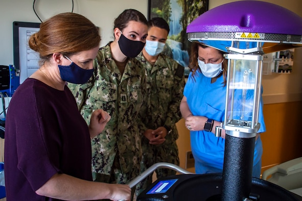 A woman wearing hospital scrubs shows a robot using ultraviolet light disinfection to another woman wearing scrubs and two people wearing military uniforms; all are wearing face masks.