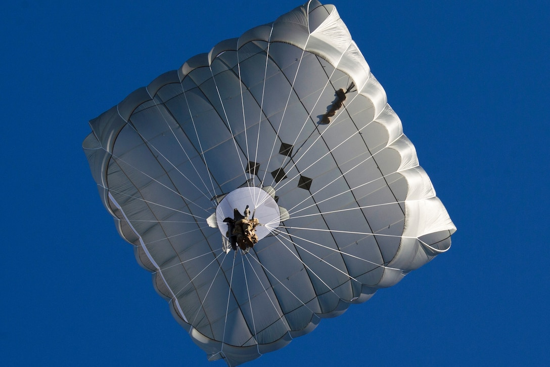 A soldier holds onto a large parachute as he floats downwards with blue sky around him.