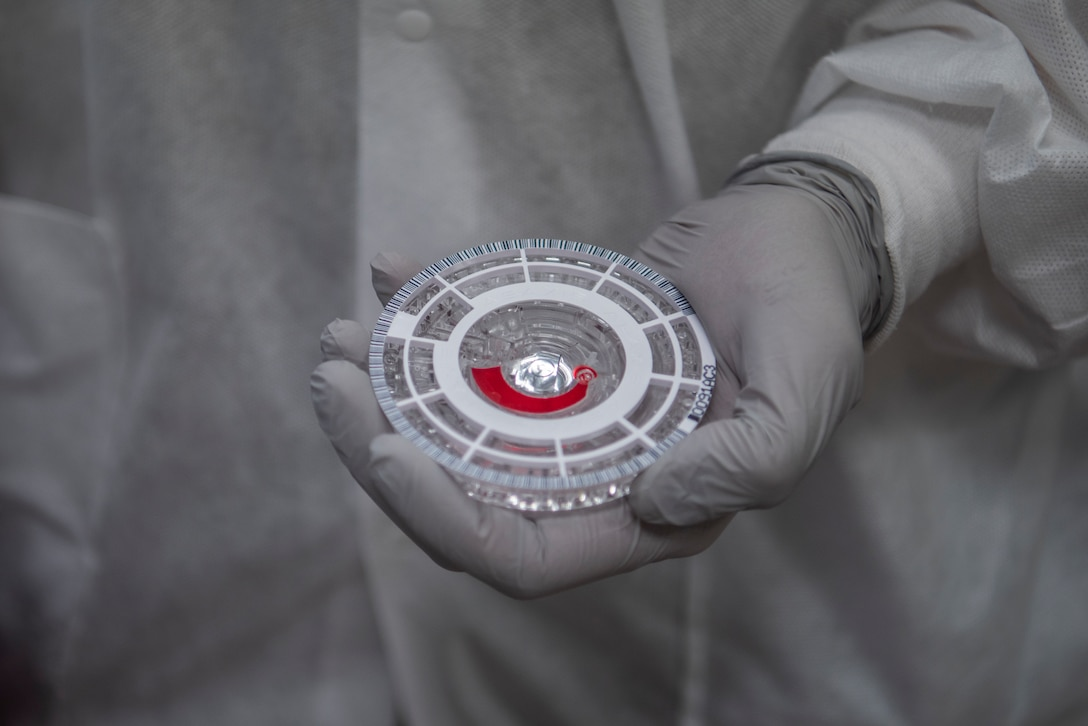 U.S. Air Force Senior Airman Moran Alexander-Luis, 86th Medical Support Squadron medical laboratory technician, holds a chemistry analyzer disc with a blood sample at Ramstein Air Base, Germany, Oct. 15, 2020. Each blood sample is separated and mixed with diluent within the disc itself. (U.S. Air Force photo by Airman 1st Class Jennifer Gonzales)