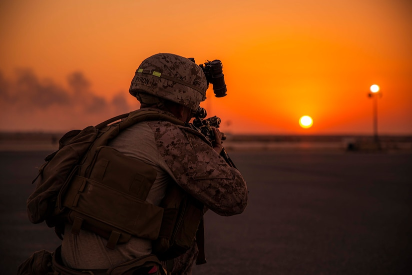 A Marine points his weapon as the sun sets in the distance.