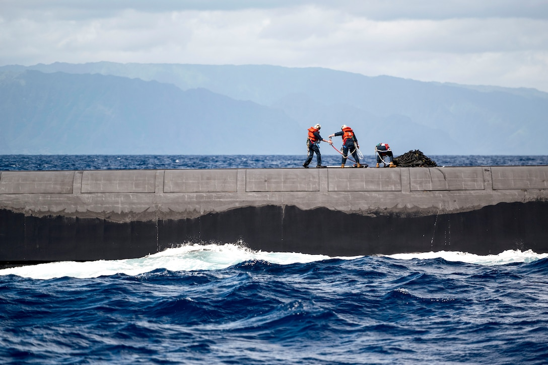 Two sailors handle cargo atop a submarine in blue water.