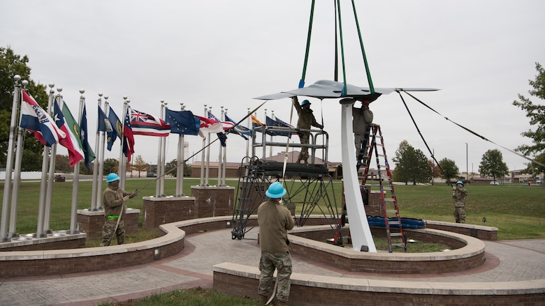 Airmen seat the B-2 static display on its pedestal in front of a set of flags.