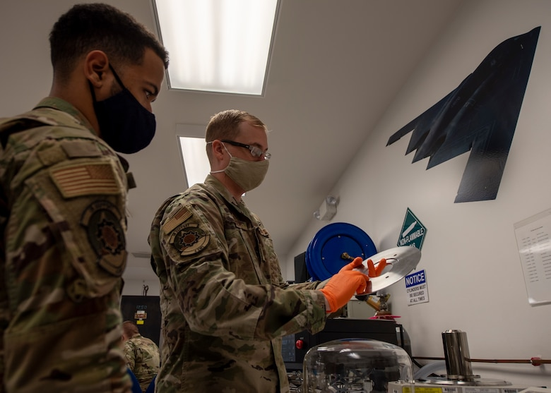 Tech. Sgt. KC Berger, 4th Component Maintenance Squadron physical dimensional element Non-commissioned Officer in Charge (right), trains the use of primary pneumatic pressure standard use to Senior Airman Thiago Santos, 4 CMS electronics technician (left), at Seymour Johnson Air Force Base, North Carolina, Oct. 19, 2020.