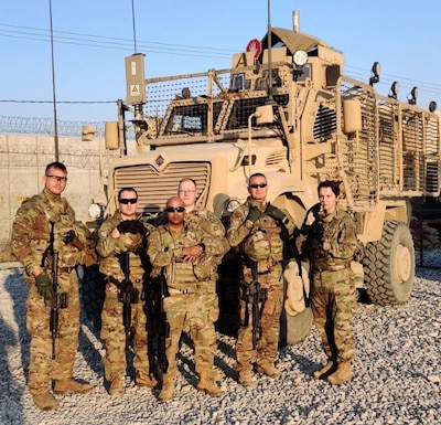 Members of BEST A24 stand next to an MRAP in Afghanistan.