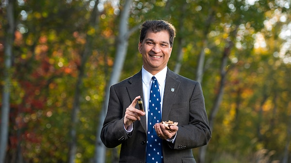 Dr. Hemant Pendse holds a small sample of wood chips and resulting synthetic crude oil.