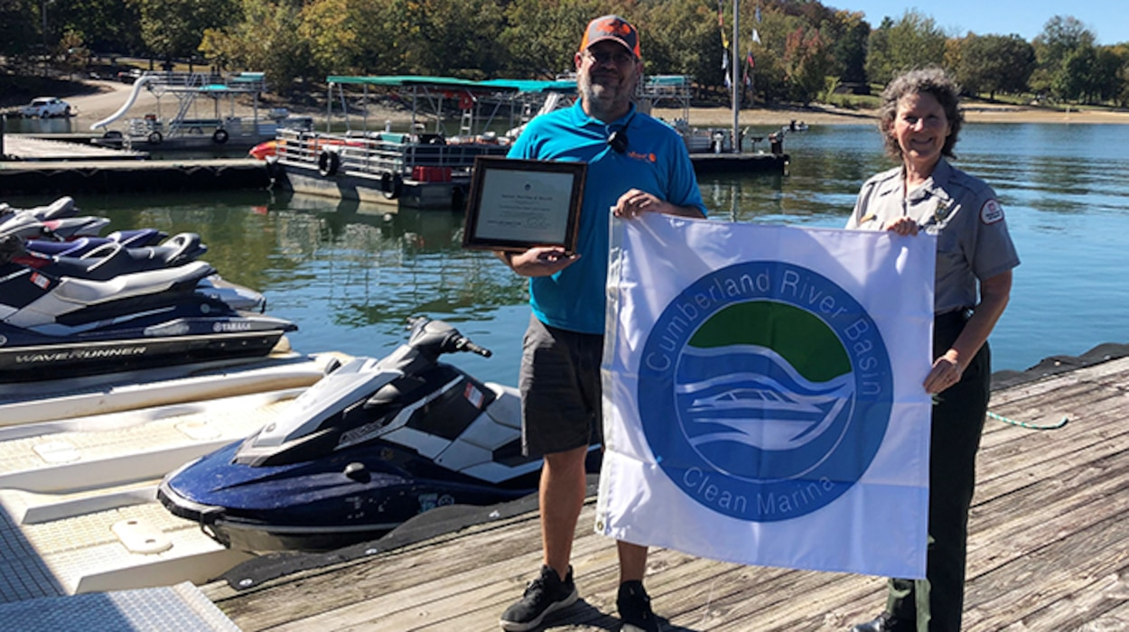 "Park Ranger Sondra Carmen presents a plaque and ""Clean Marina"" flag to Sunset Marina Assistant Manager Brad Richardson at Dale Hollow Lake in Monroe, Tennessee, Oct. 13, 2020. (USACE Photo by Daniel Clark)"
