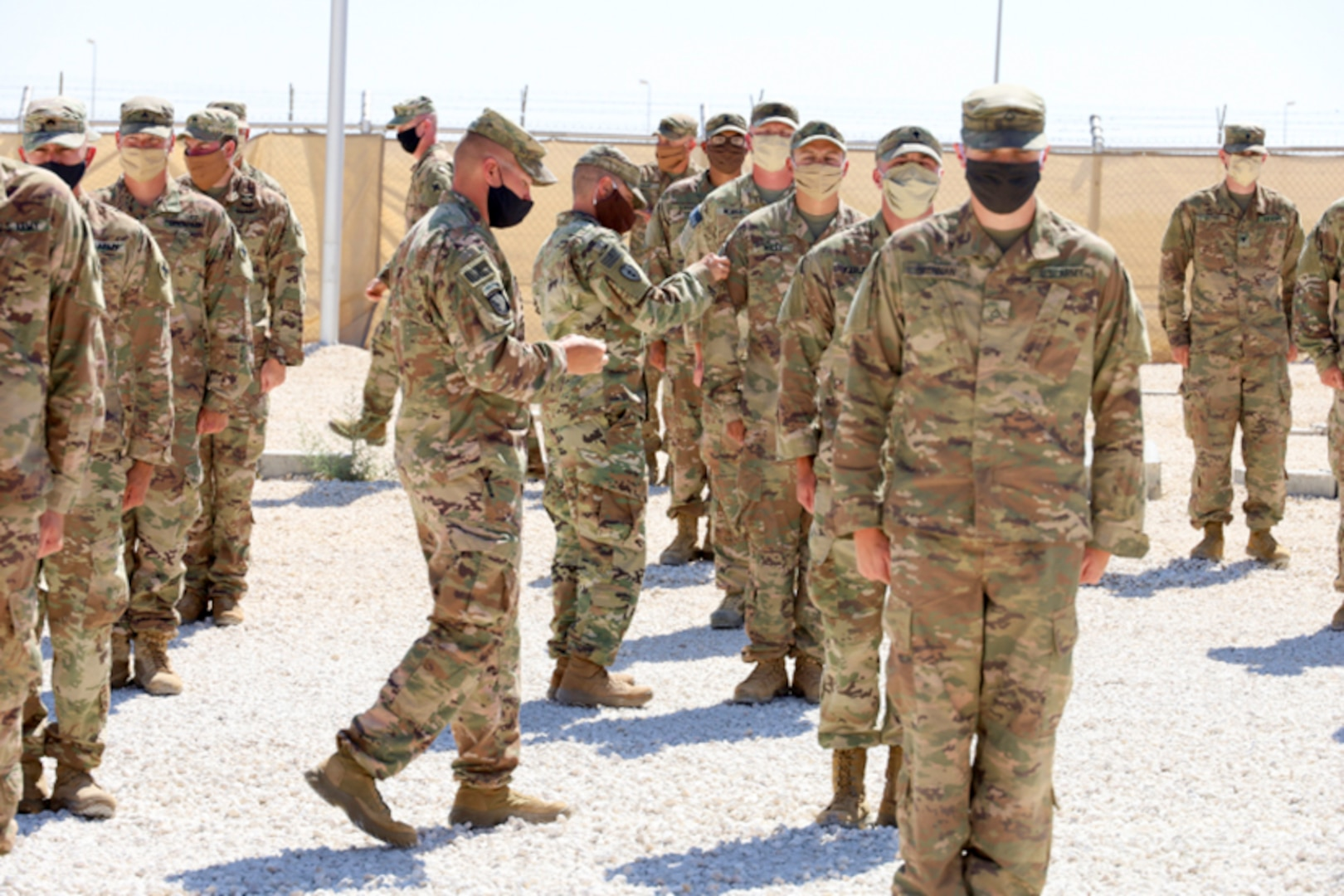 Senior non-commissioned officers with Headquarters and Headquarters Company, 2nd Battalion, 130th Infantry Regiment, based in Marion, Illinois, present the Soldiers with combat patches.