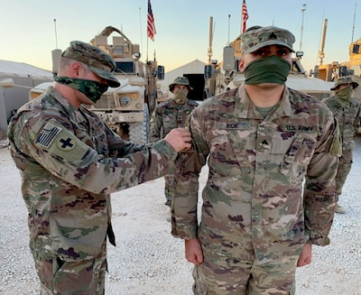 Command Sgt. Maj. Jeffery Sowash, of Springfield, Missouri, 2nd Battalion, 130th Infantry Regiment's senior enlisted leader, presents 1st Lt. Mike Ferrer, of Fairview Heights, Illinois, with his combat patch which will be displayed on his right shoulder.
