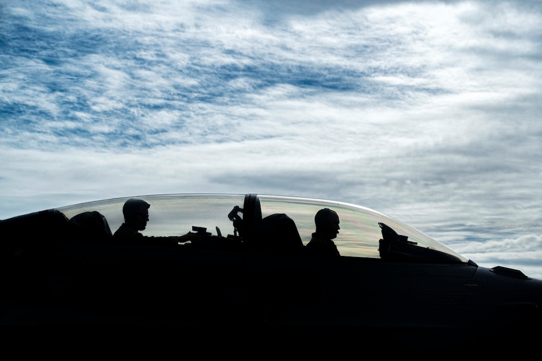 Two airmen, shown in silhouette, sit inside of a military aircraft.