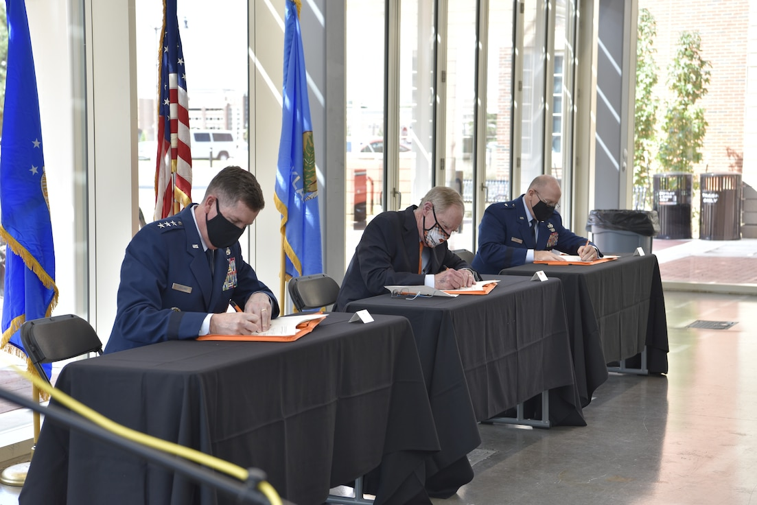 Three people signing contracts behind desks