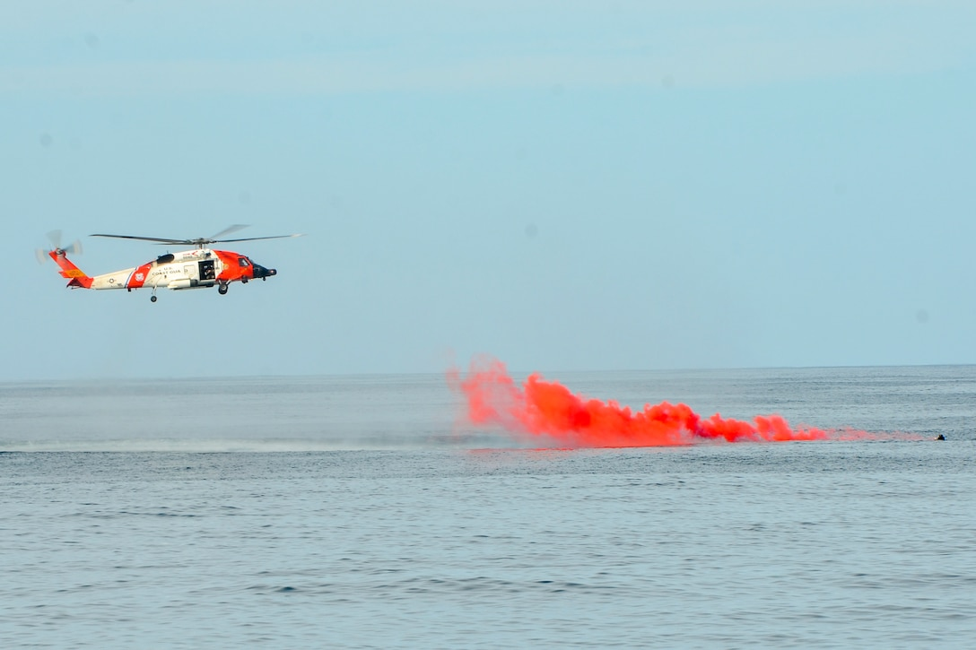 A helicopter flies near a cloud of orange smoke floating over a body of water.