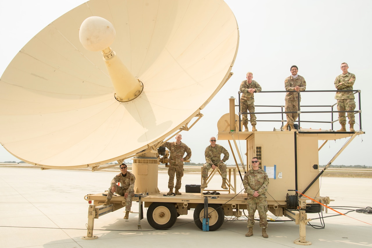 Airmen pose for a photo in front of a satellite terminal.